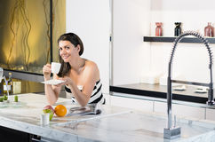 Coffee in New Kitchen. Beautiful woman enjoying new kitchen Royalty Free Stock Image