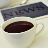 Coffee and news in the tablet. Closeup of a cup of coffee and a tablet computer with the word news in its screen stock image