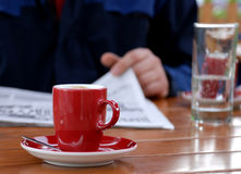 Coffee and newspaper. Red cup of coffee and newspaper on wooden table Stock Image