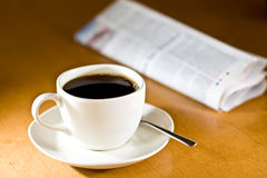 Coffee & Newspaper. Cup of steaming coffee with newspaper in background Stock Photos