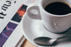 Coffee and newspaper. Espresso in a cup with newspaper in background royalty free stock images