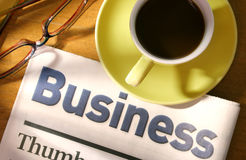 Coffee, Newspaper and Eyeglasses on Desk Stock Images