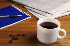 Coffee, newspaper and notepad Stock Photo