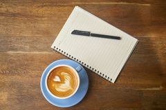 Coffee next to notepad and pen