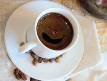 Black coffee with foam in the form of smiles in a white cup Stock Images
