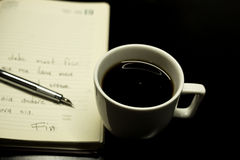 Coffee night. Coffee on table with notebook and pen Stock Photos