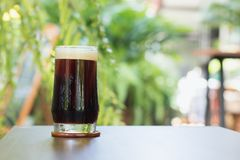 Coffee Nitro Cold Brew in glass on table outdoor cafe. Coffee Nitro Cold Brew on table in outdoor cafe Royalty Free Stock Photography