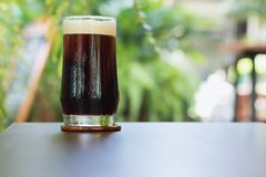 Coffee Nitro Cold Brew in glass on table outdoor cafe. Coffee Nitro Cold Brew on table in outdoor cafe Royalty Free Stock Photo