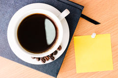Coffee and note pad on wood table Royalty Free Stock Photo