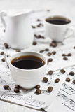 Coffee on note sheets. White coffee cups and creamer on old note sheets Stock Photography