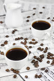 Coffee on note sheets. White coffee cups and creamer on old note sheets Royalty Free Stock Photography