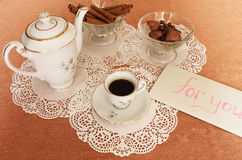 Coffee with a note. Still Life with cup of coffee, coffee pot, vase with sweets, on the lace salfete Royalty Free Stock Photos