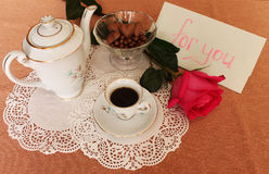 Coffee with a note. Still Life with cup of coffee, coffee pot, vase with sweets and rose on lace salfete Royalty Free Stock Photo