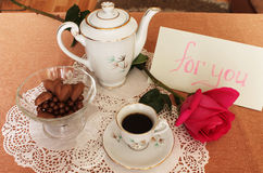 Coffee with a note. Still Life with cup of coffee, coffee pot, vase with sweets and rose on lace salfete Stock Photography