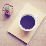 Coffee on notebook and cactus with retro filter effect Stock Images