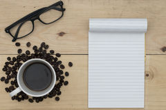 Coffee, notebook and glasses on wood table Royalty Free Stock Photo