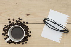 Coffee, notebook and glasses on wood table Stock Photos