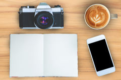 Coffee,notebook,mobile phone and camera on teak wood texture background. Coffee,notebook,mobile phone and camera on teak wood texture background Royalty Free Stock Images