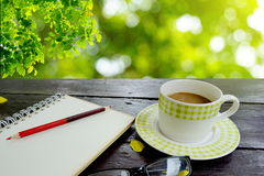 Coffee and notebook page with pencil on wooden table over nature green leaves Royalty Free Stock Photography