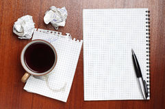 Coffee, notebook, pen and crumpled paper. On table Stock Image