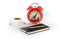 Coffee, a notebook, a pen and a red alarm clock Royalty Free Stock Photo