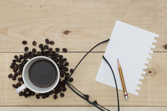 Coffee, notebook, pencil and glasses on wood table Stock Images