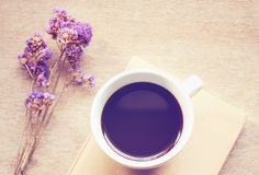 Coffee on notebook with statice flowers, retro filter effe Royalty Free Stock Image