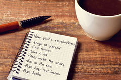 Coffee and notepad with a list of new years resolutions. A cup of coffee and a notebook with a list of new years resolutions, such as laugh at yourself, give Royalty Free Stock Images