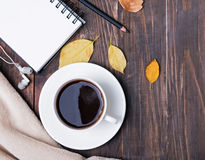 Coffee, notepad, pensil and autumn leaves on the wooden backgrou. Autumn still life. Coffee, notepad, pensil and leaves on the wooden background, top view Stock Photos