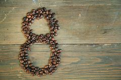 Coffee number eight. Number eight made with coffee beans on a wooden plank Royalty Free Stock Photo