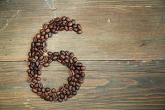 Coffee number six. Number six made with coffee beans on a wooden plank Royalty Free Stock Image