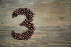 Coffee number three. Number three made with coffee beans on a wooden plank Royalty Free Stock Images