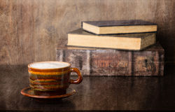 Coffee and old books. Coffee and a stack of old books. Retro look with added texture Stock Photography