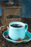 Coffee and old coffee mill. Coffee in the teal mug and old coffee mill with cinnamon and star anise. Selective focus Stock Photo