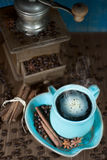 Coffee and old coffee mill. Coffee in the teal mug and old teal mill with cinnamon and star anise. Selective focus Royalty Free Stock Image