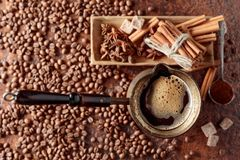 Coffee in an old copper coffee maker with cinnamon, anise and  sugar. Coffee in an old copper coffee maker with cinnamon, anise and pieces of brown sugar. View royalty free stock images
