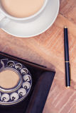 Coffee with old land line and pen. Close-up of coffee with old land line and pen on table Royalty Free Stock Image