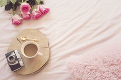 Coffee, old vintage camera in bed on pink sheets. Roses and notebooks around. Freelance fashion home femininity workspace in flat. Lay style royalty free stock photo