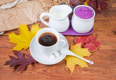 Coffee on old wooden table with autumn leaves and scarf. White cup of freshly brewed coffee on saucer with ceramic spoon and sugar, sugar bowl and jug of milk on stock photography