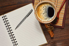 Coffee and opened notebook in horizontal top view. Opened notebook or diary, cup with coffee, some spices on the bamboo ma and wooden table Stock Image