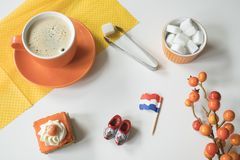 Coffee, orange cake, flag and wooden shoe for typical Dutch event Koningsdag, Kings day. Cup of coffee and cake with orange frosting. Dutch table scene with royalty free stock photos