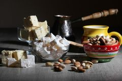Coffee and oriental sweets. A mug of coffee and different oriental sweets: turkish delight, halva, almond and pistachio royalty free stock photo
