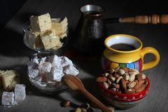 Coffee and oriental sweets. A mug of coffee and different oriental sweets: turkish delight, halva, almond and pistachio royalty free stock photos
