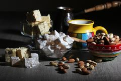Coffee and oriental sweets. A mug of coffee and different oriental sweets: turkish delight, halva, almond and pistachio stock image