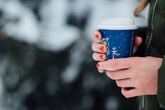 Girl holds coffee in hands in winter cold day. Stock Photography