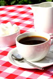 Coffee outside on table. Photograph of a cup of coffee with milk and sugar cubes Stock Images