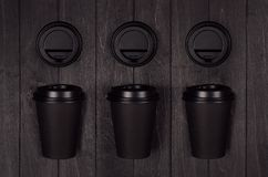Coffee packing mockup - set fo three black paper cups and blank caps on dark black wood board, coffee shop interior. stock image