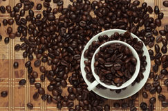 Coffee pad. White cup and saucer filled with coffee beans royalty free stock images