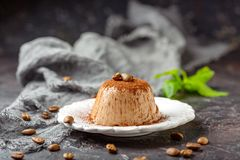 Coffee Panna cotta sprinkled with cocoa powder. Plate with coffee Panna cotta on milk chocolate sprinkled with cocoa powder and decorated with coffee beans on a stock photography