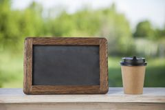 Coffee paper cup with chalk board, on wood table, summer day bac. Kground Stock Photography